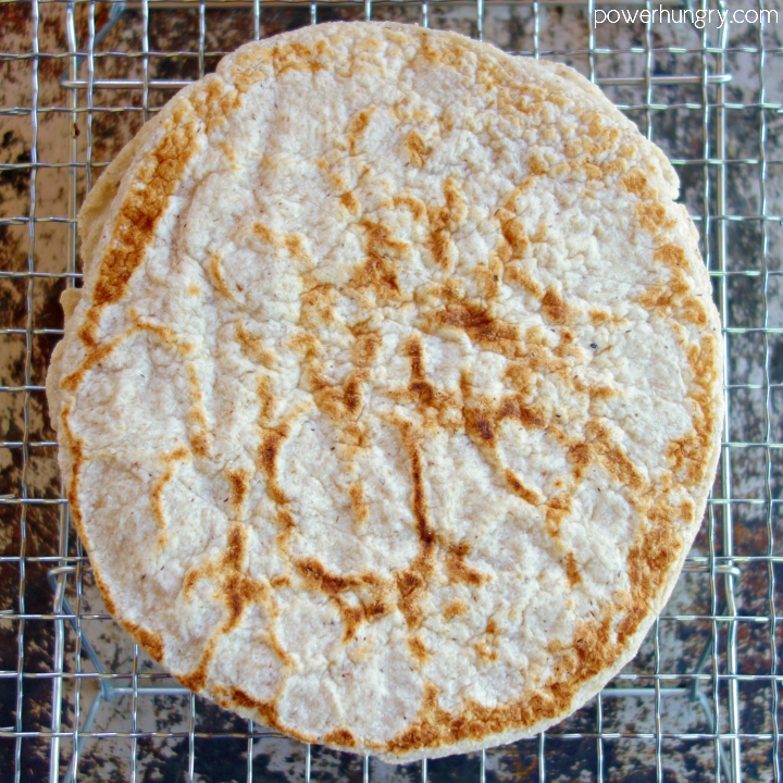 puffed 2-ingredient coconut flour tortilla cooling on a metal cooling rack