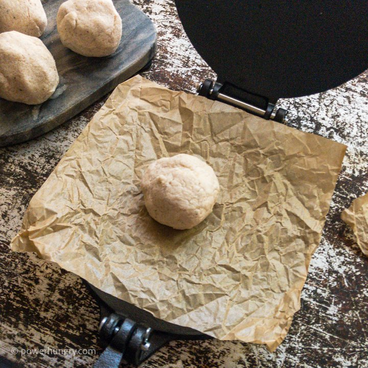 a ball of cassava flour tortilla dough on a piece of parchment paper, about to be pressed by a tortilla press