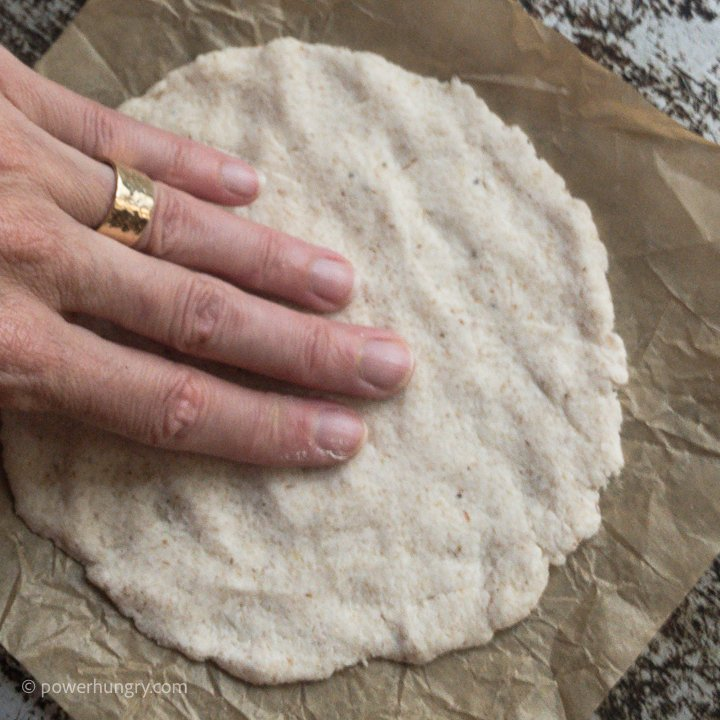 2 ingredient cassava flour tortilla being pressed out by hand on a piece of parchment paper