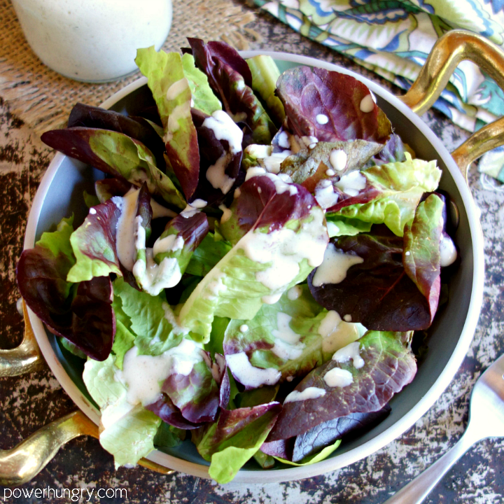 Metal bowl with gold handles filled with mixed baby lettuce and topped with a cashew based oil-free vinaigrette