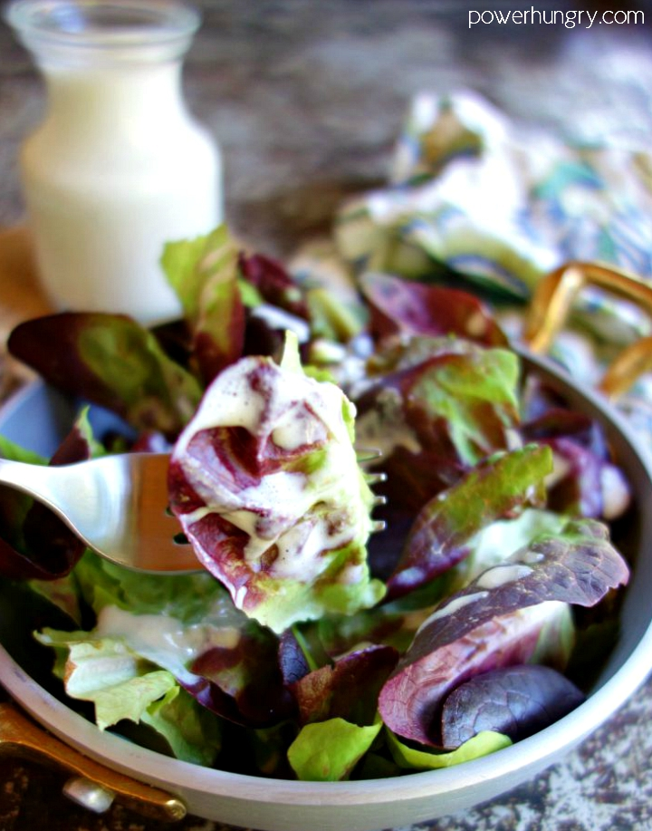Cashew salad dressing drizzled over mixed baby lettuce in a metal dish