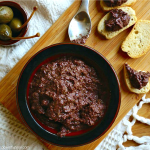 healthy kalamata olive tapenade ina dark bowl alongside pieces of small toasts