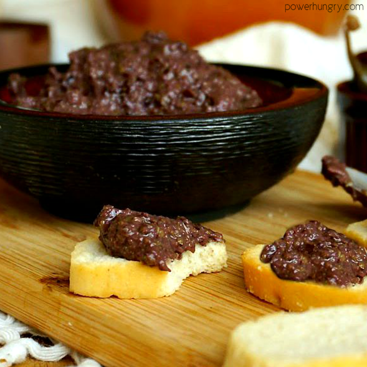 close up of a side view of olive tapenade with toasts, spread with the tapenade, in the foreground