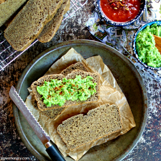 overhed shot of slices of chickpea flour flax bread with a green pea spread
