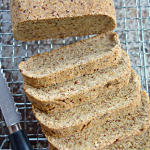 overhead shot of keto vegan coconut flour bread on a wire cooling rack, with a bread knife alongside