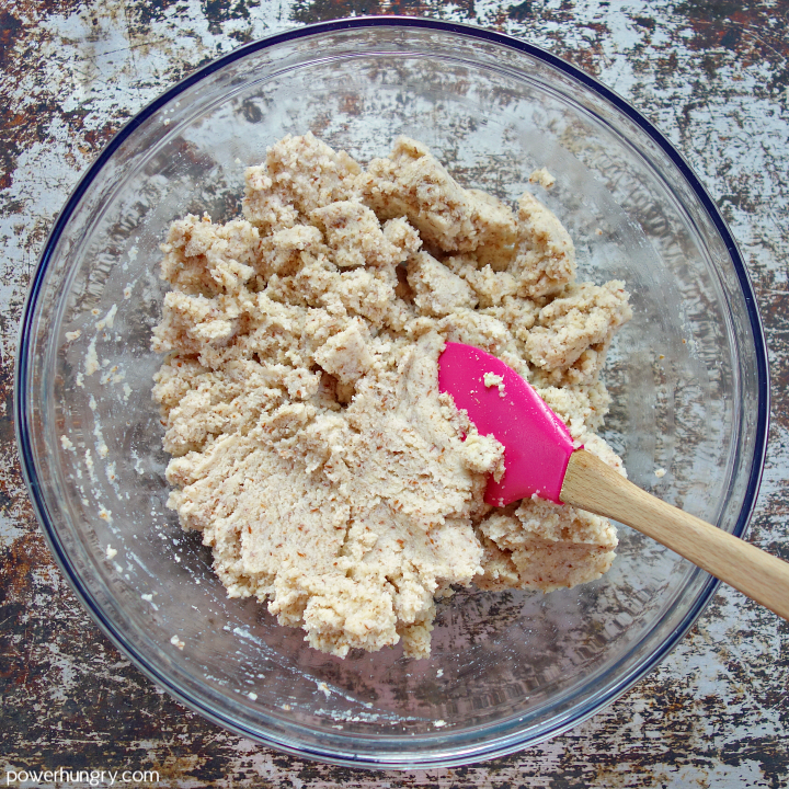 stirred dough for coconut flour bread in a glass bowl with rubber spatula inside