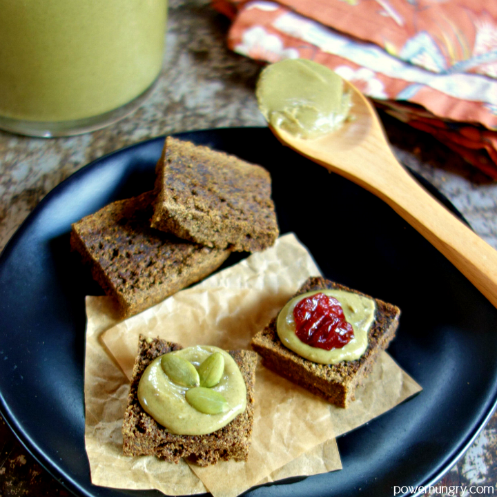 a black plate with flax crackers topped with pepita butter and toppings