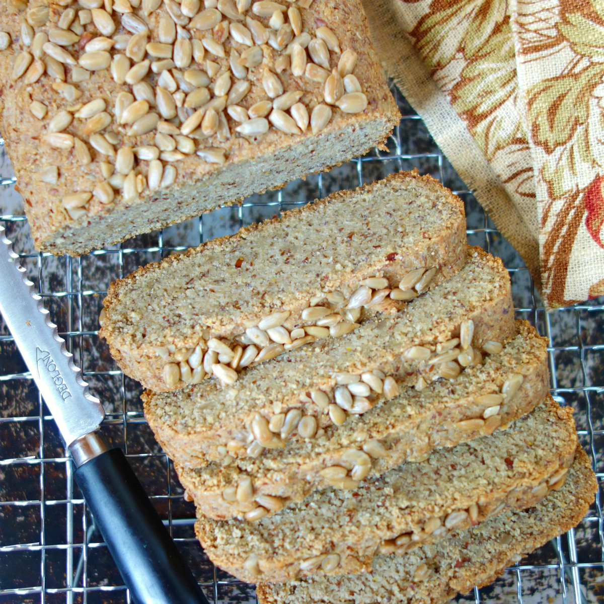 sunflower seed bread on a metal cooling rack with a bread knife and floral napkin alongside