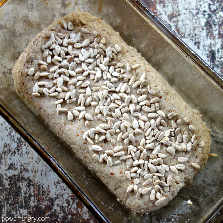 Sunflower seed bread dough in a glass loaf pan, topped with sunflower seeds