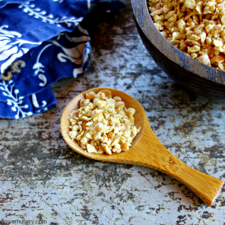 a wooden spoon filled with chickpea breadcrumbs , with a bowl of the crumbs and a navy napkin in the background