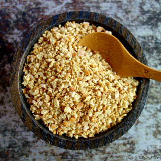 dark wooden bowl filled with chickpea breadcrumbs, with a wooden spoon inserted into crumbs