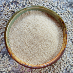 DIY sunflower seed flour in an earth-tone pottery bowl, surrounded by shelled, raw sunflower seed kernels