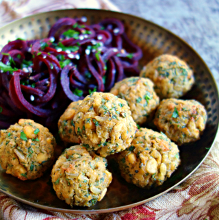 yellow split pea meatballs on a hammered metal plate with beet noodles alongside