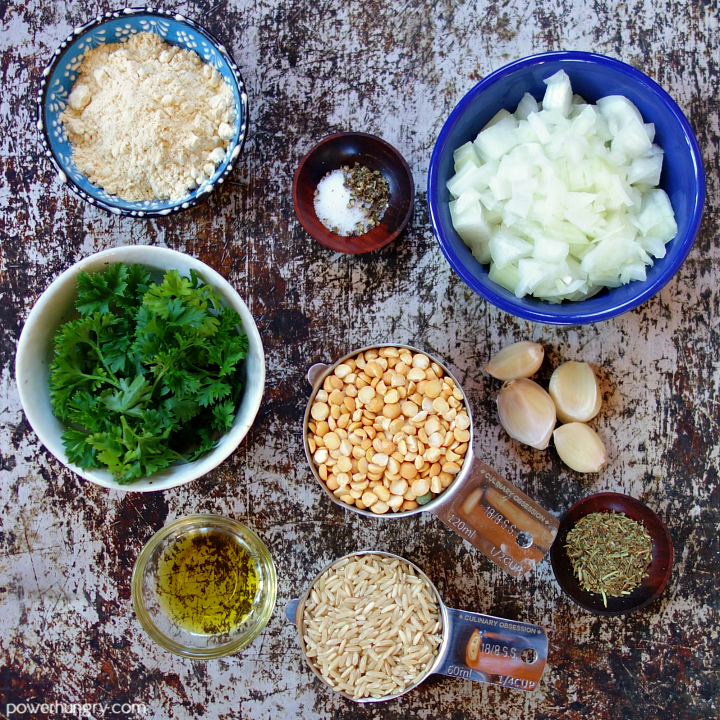 ingredients for baked split pea meatballs laid out, in small bowls, on a baking sheet