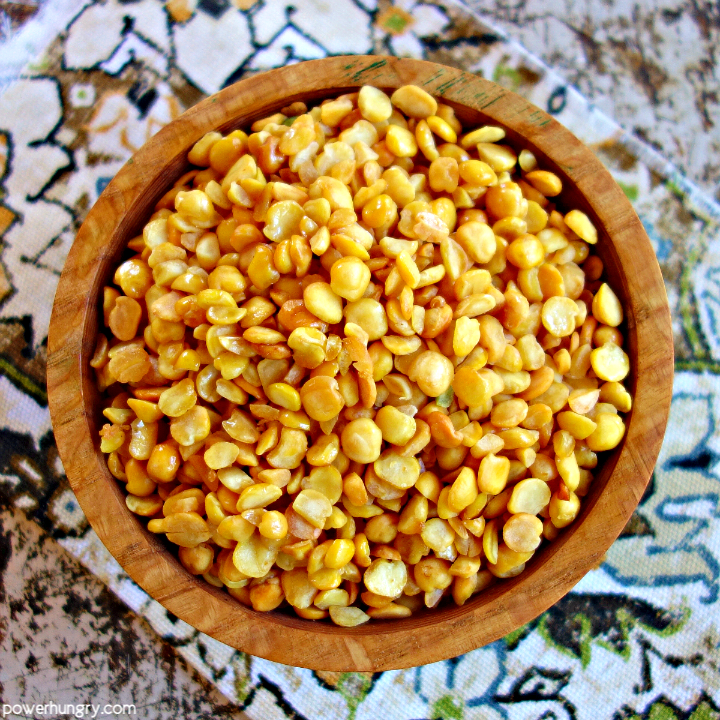 a wooden bowl filled with baked crispy split peas