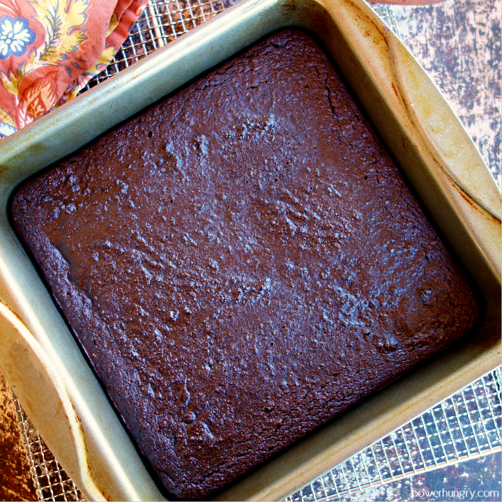 baked brownies, cooling in a baking pan, atop a wire cooling rack