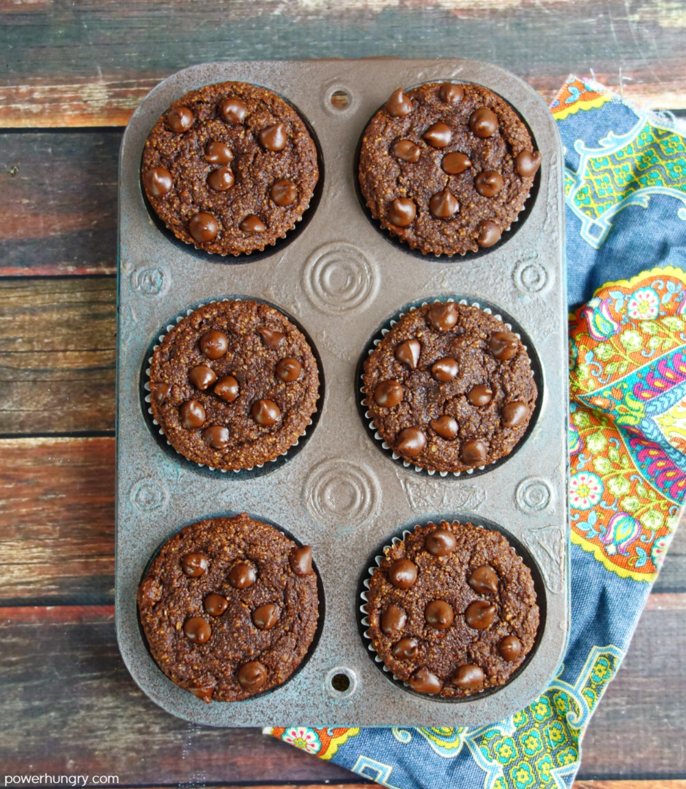 6chocolate muffins in an antique muffin tin, set on top of a wooden board with a colorful napkin alongside