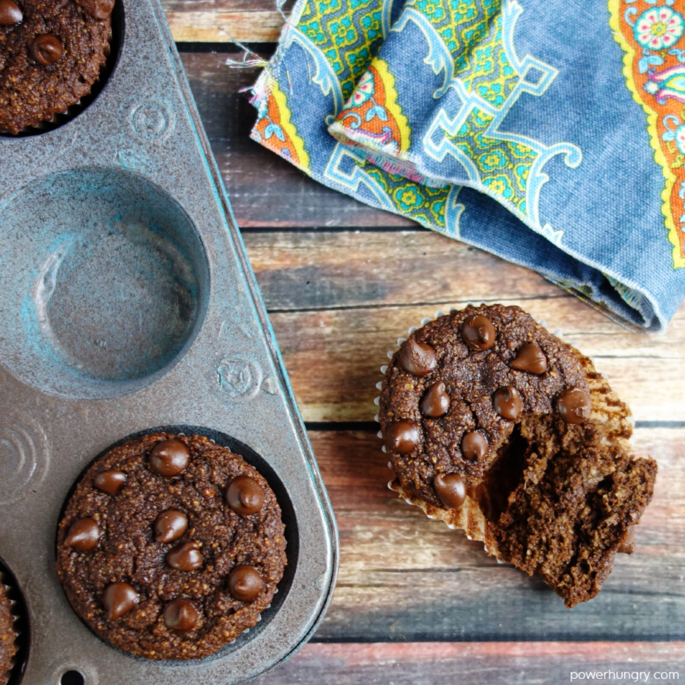 overhead shot of chocolate muffins, with one outside of the muffin tin