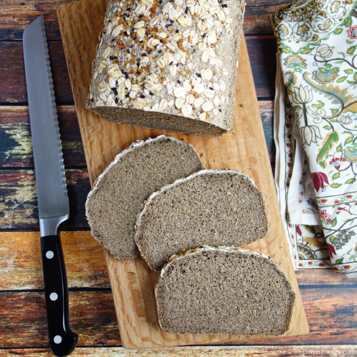a sliced loaf of gluten-free bluckwheat bread on an artisan wood cutting board.