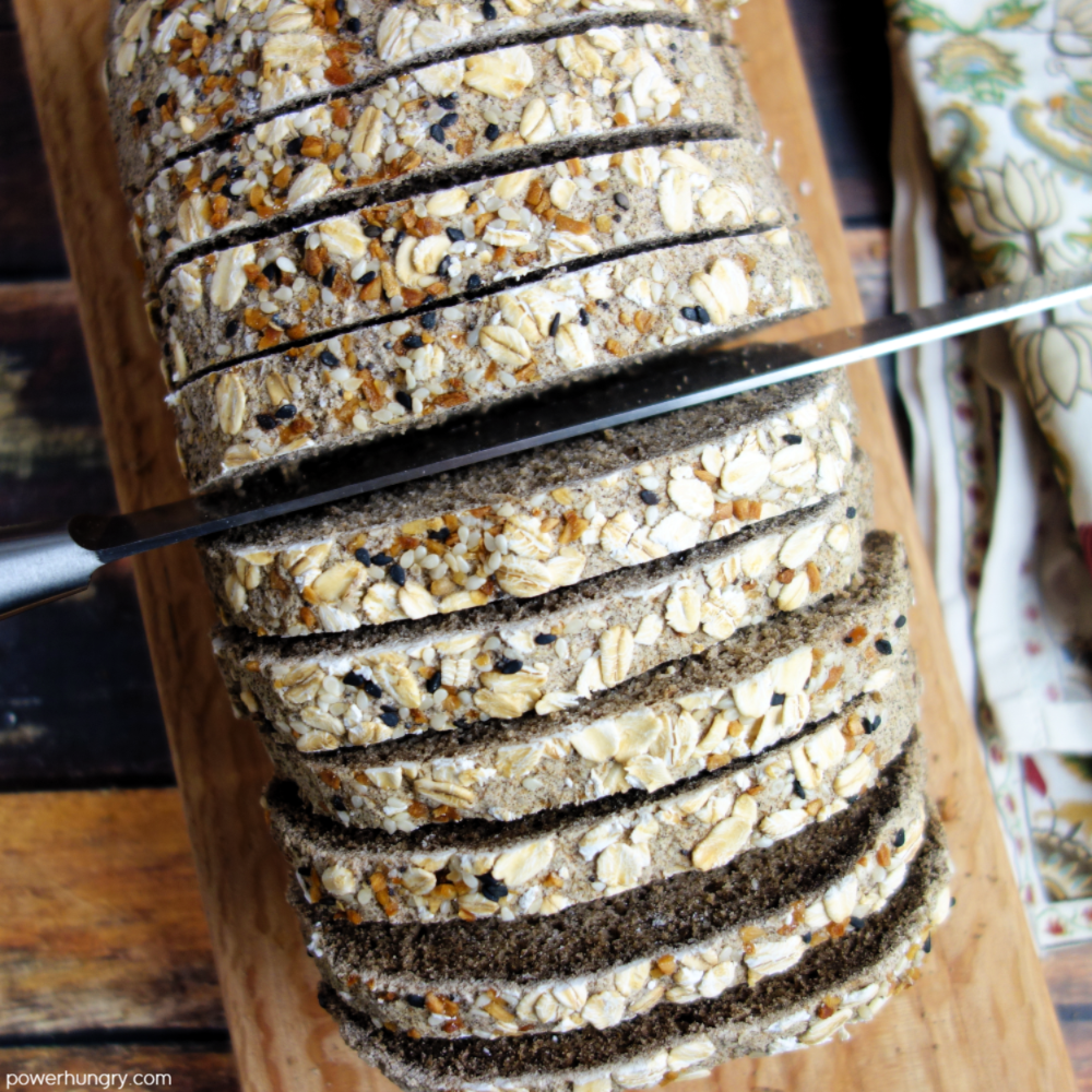 overhead shot of buckwheat bread being sliced with a serrated knife