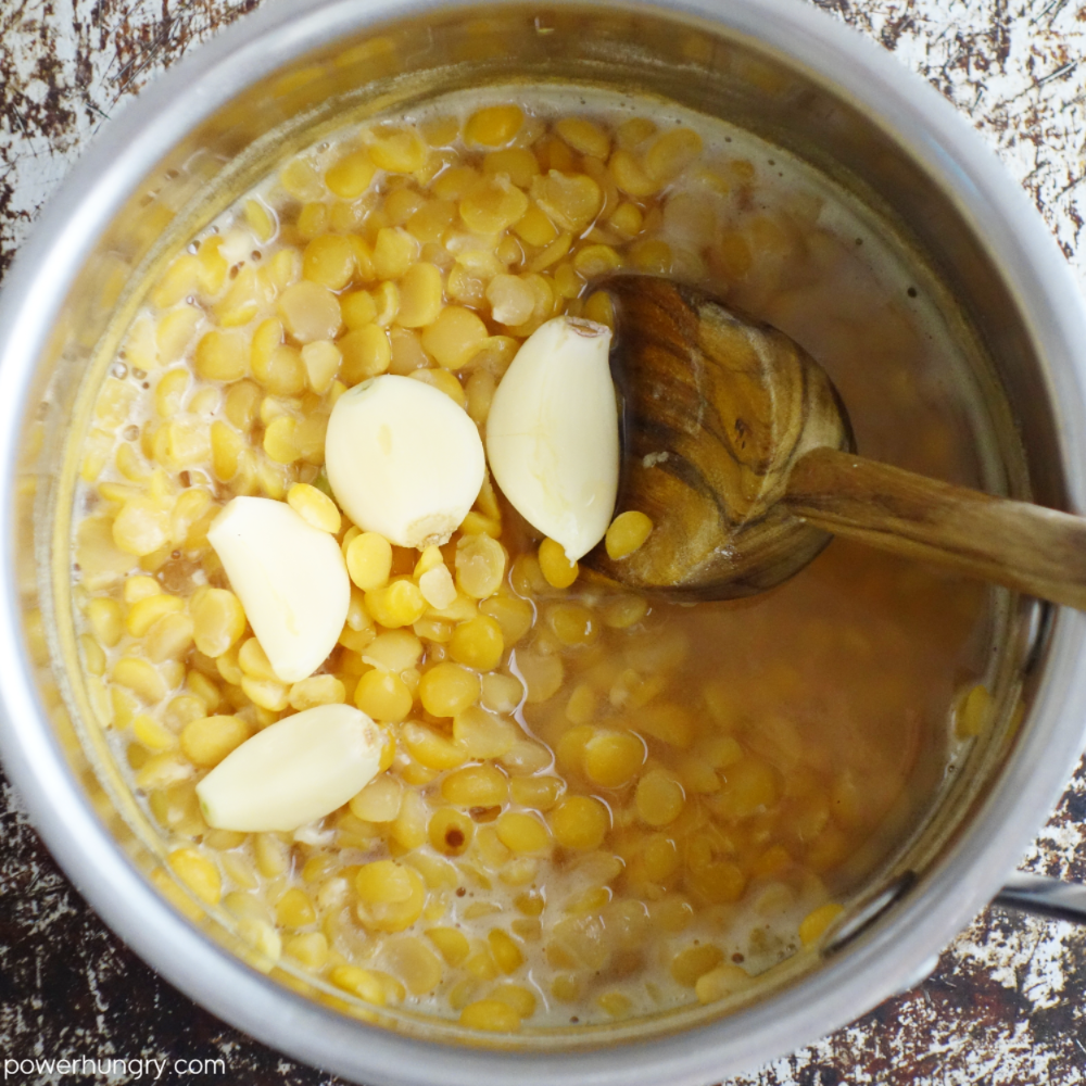 saucepan filled with cooked yellow split peas and garlic cloves