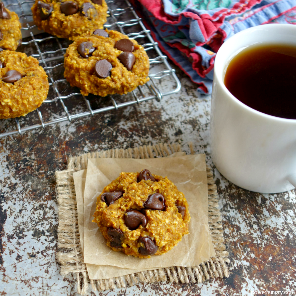 pumpkin cookie on a piece of brown parchment with more cookies on a rack in the background