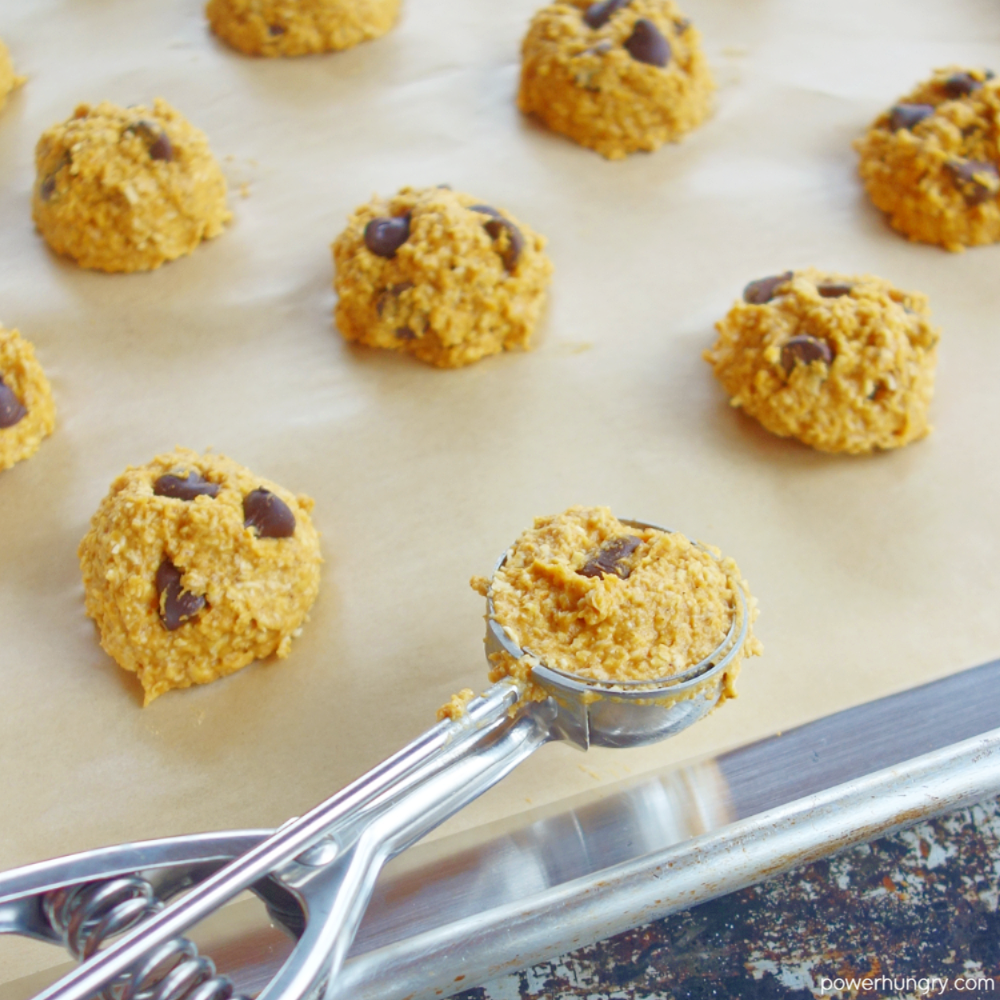 baking sheet with mounds of cookie dough and a cookie scoop in the foreground