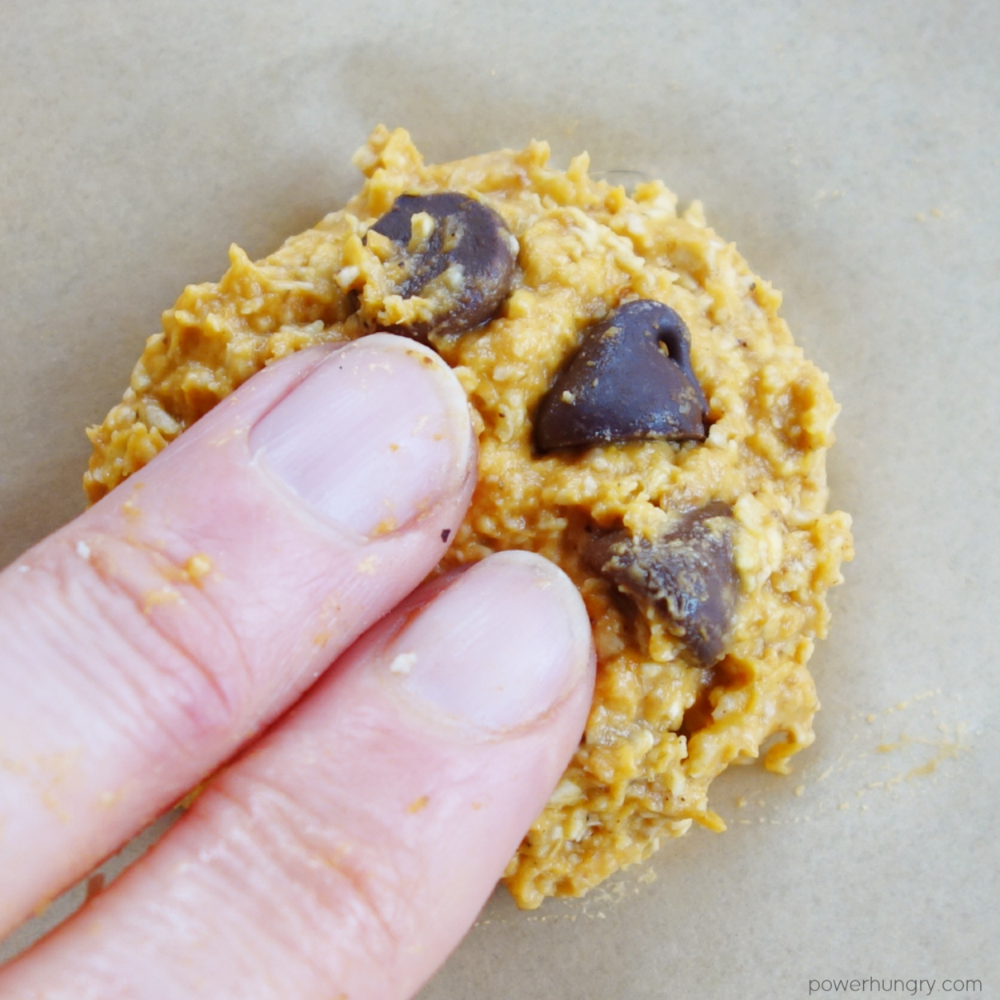close up of a mound of pumpkin cookie dough being flattened with fingertips