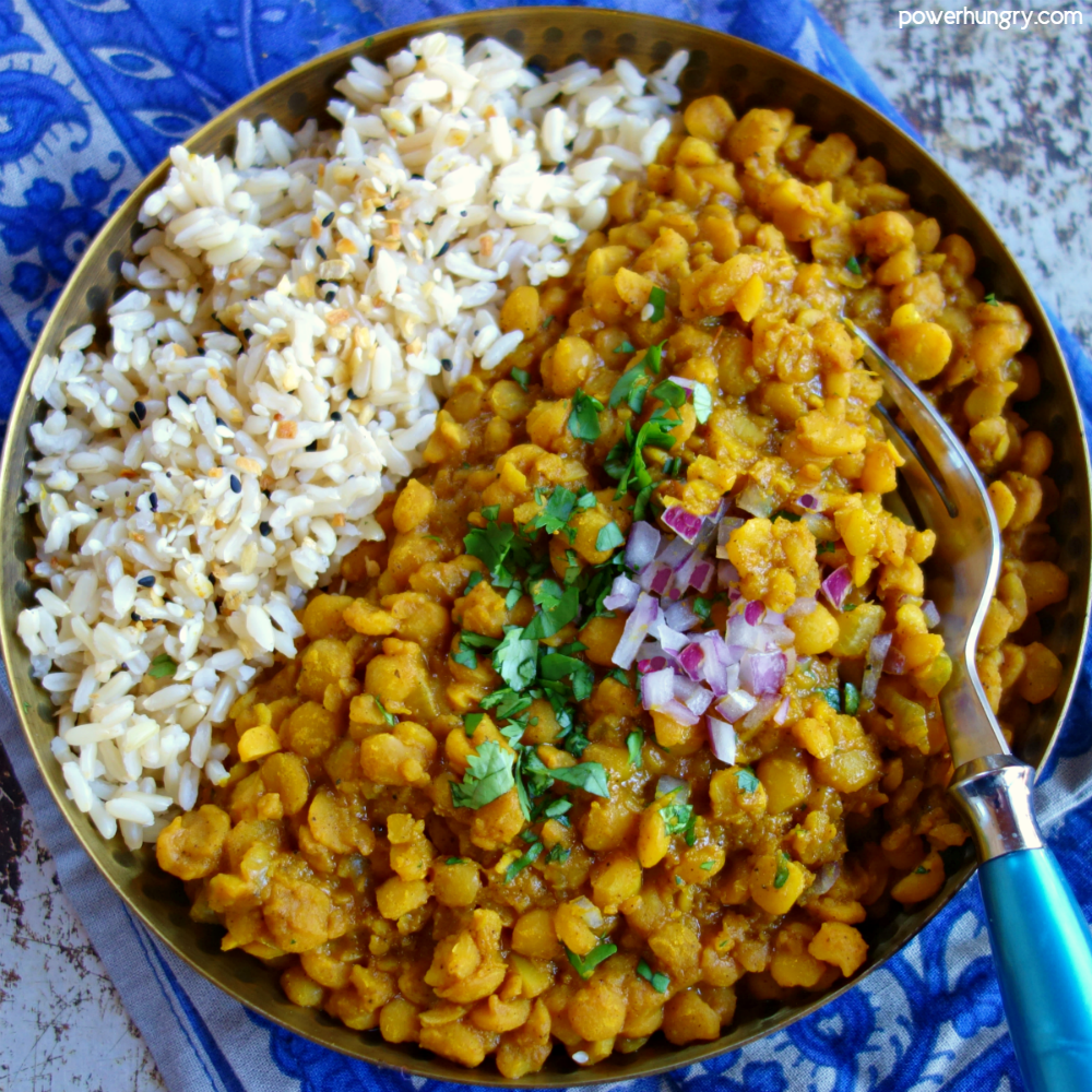 overhead shot of split pea curry in a metal bowl with rice alongside