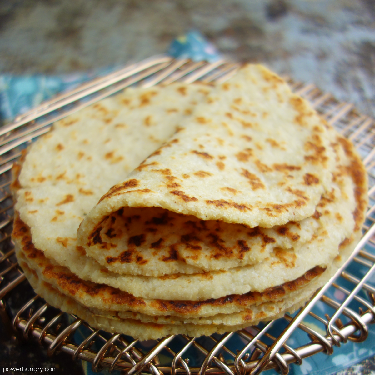 stack of almond tortillas on a copper wire rack