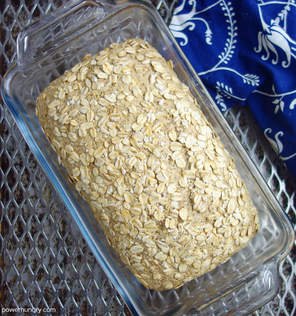baked loaf of gluten free vegan bread in a glass loaf pan
