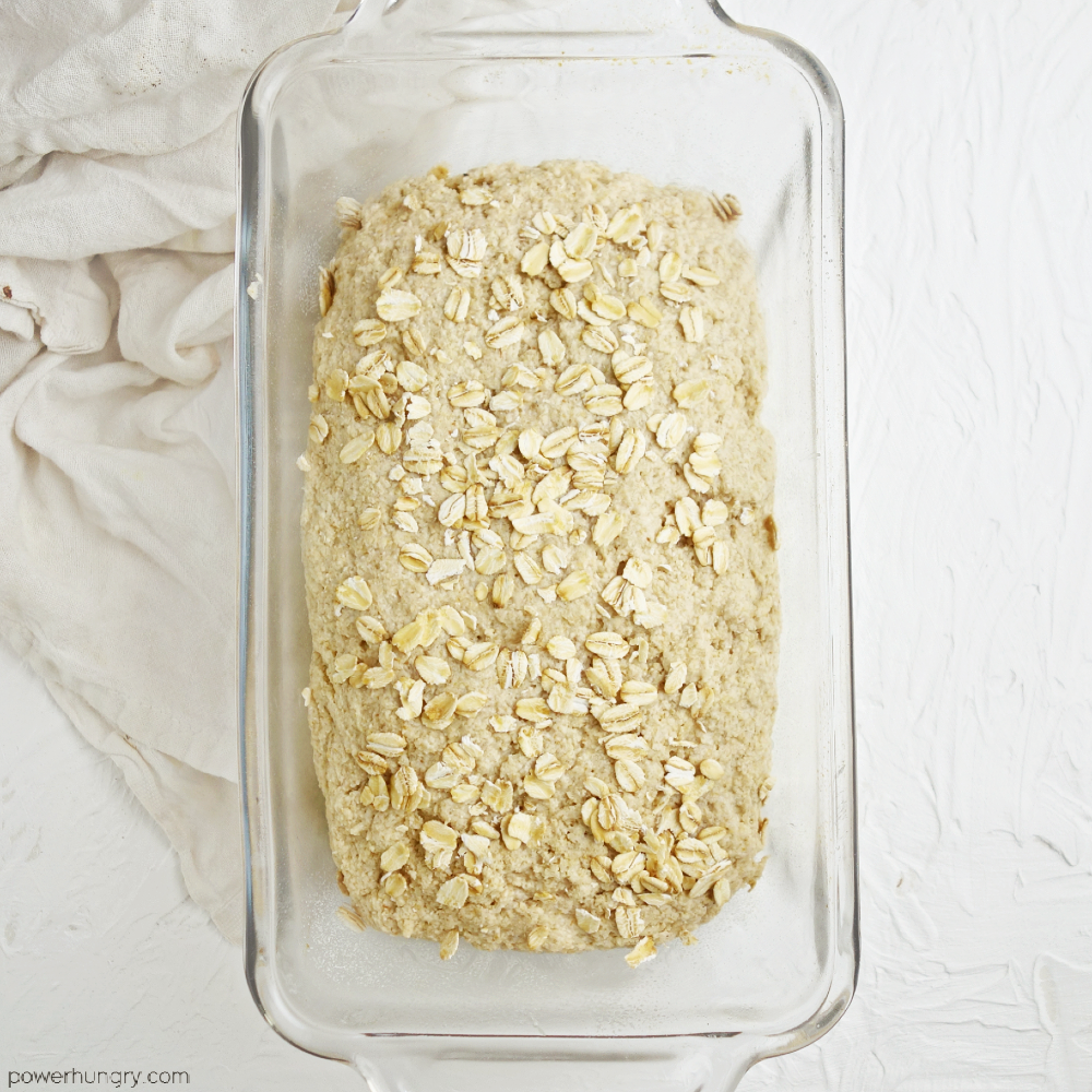 unbaked oat bread in a glass loaf pan