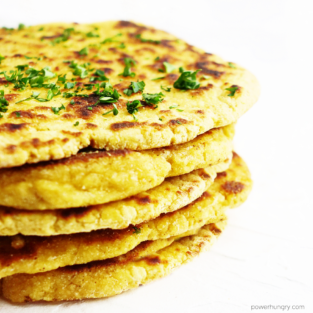 stack of chickpea flour naan sprinkled with finely chopped parsely