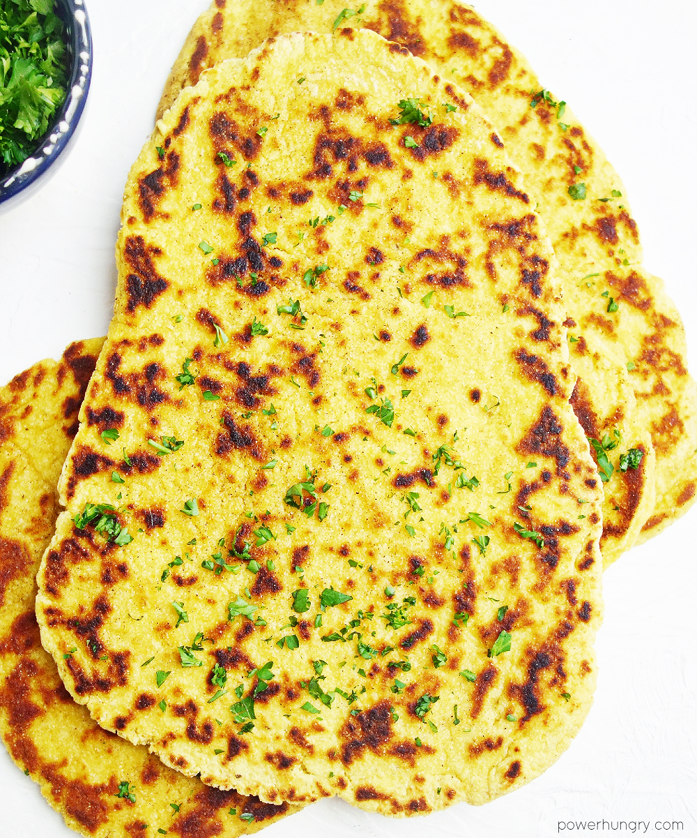 overhead shot of chickpea flour naan with a small bowl of chopped parsely leaves