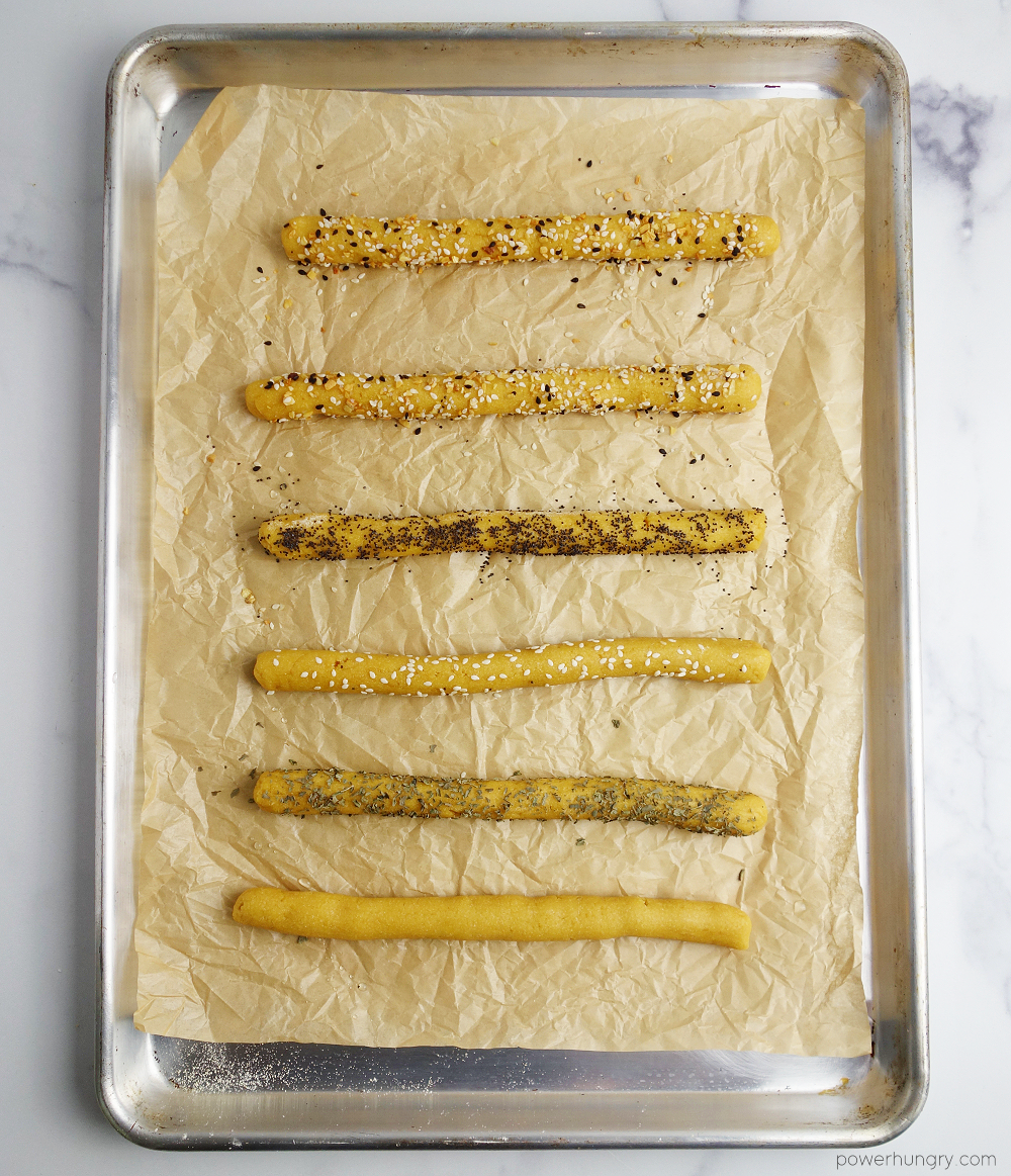 unbaked chickpea flour dough ropes, rolled in seeds and herbs, on a parchment paper lined baking sheet