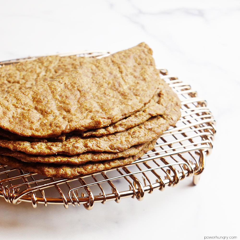 Flax tortillas stacked on a copper wire cooling rack
