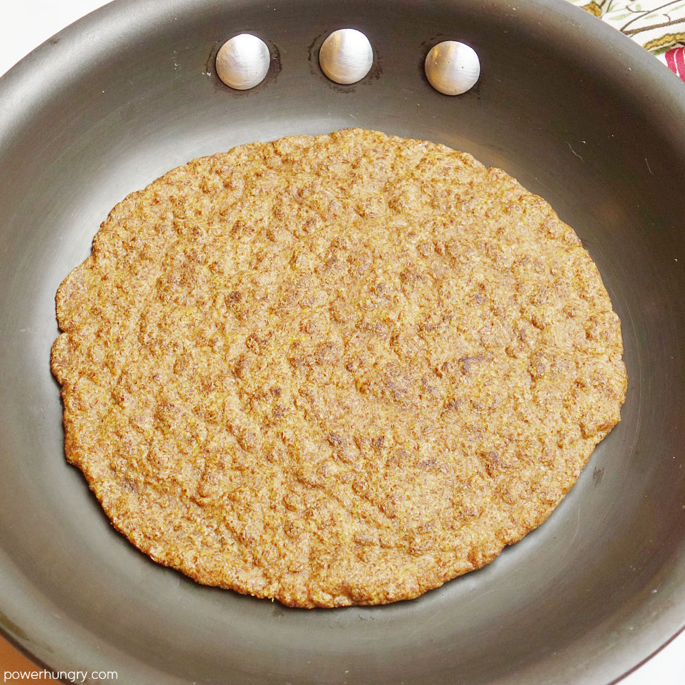flax tortilla being cooked n a cast iron skillet