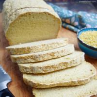 a loaf of millet sandwich bread, sliced, on a cutting board