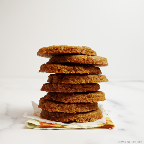 stack of 8 flax shortbread cookies on a floral napkin with a white background