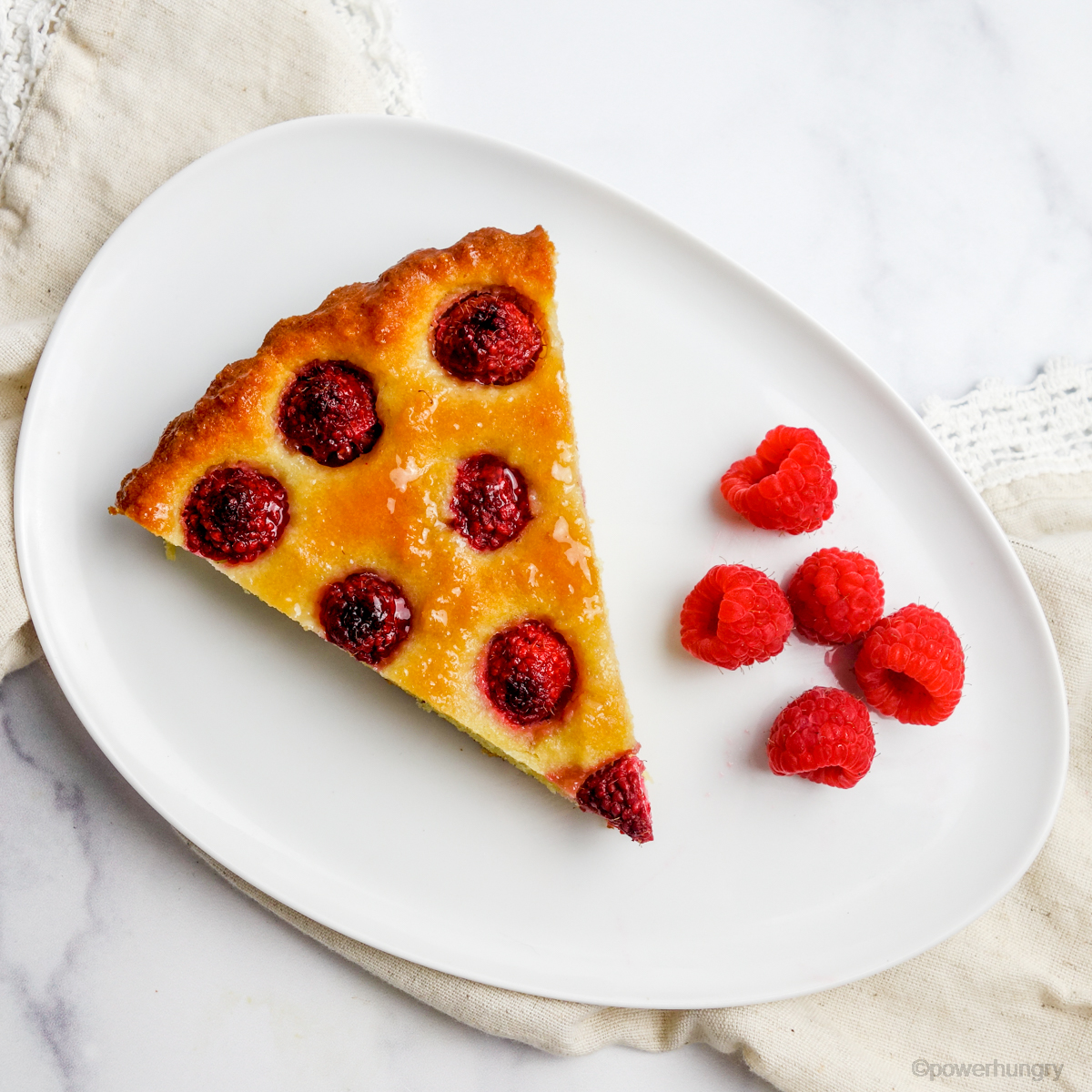 singleslice of vegan no-crust raspberry almond tart on a white plate with fresh raspberries