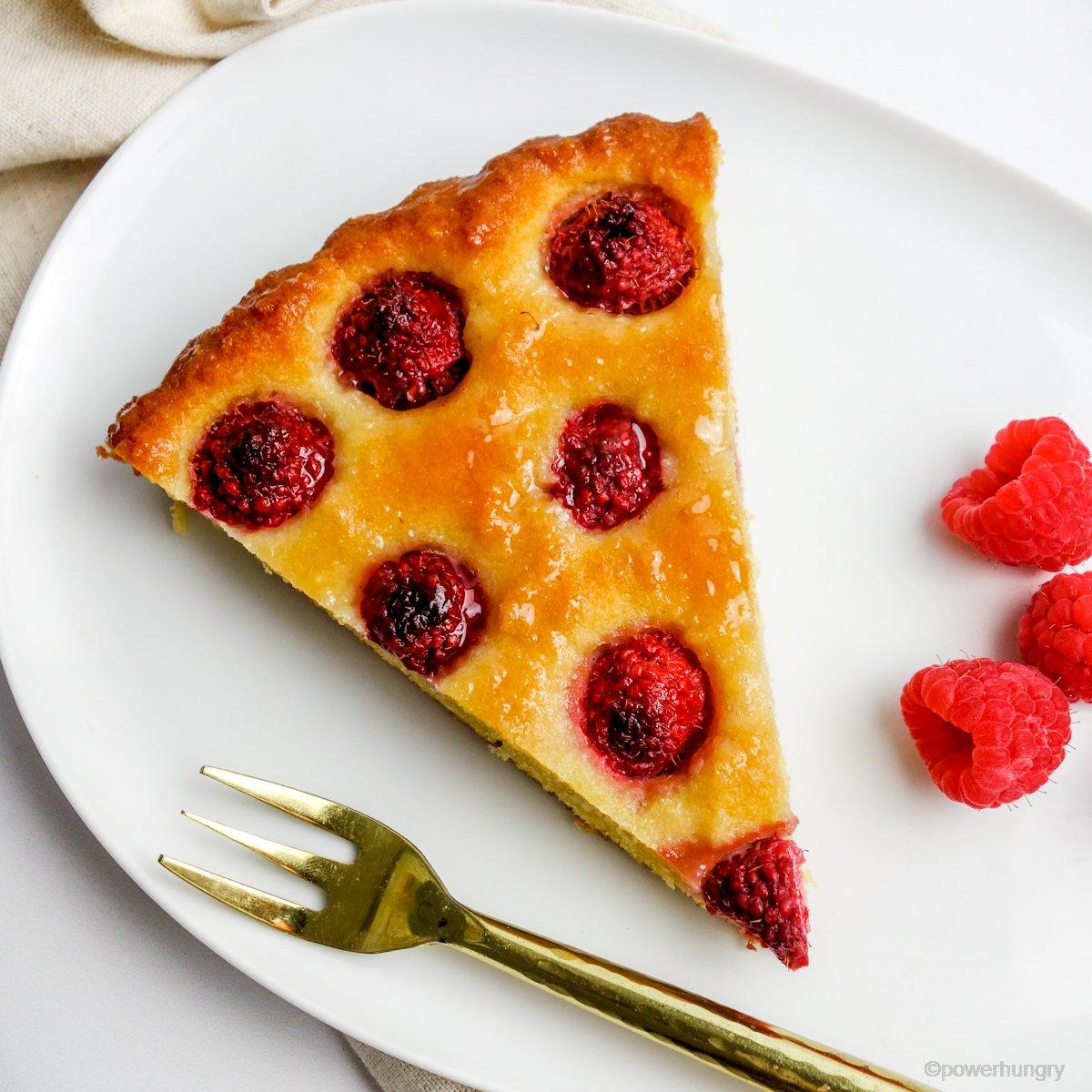 a slice of vegan no-crust raspberry almond tart on a white plate with fresh raspberries