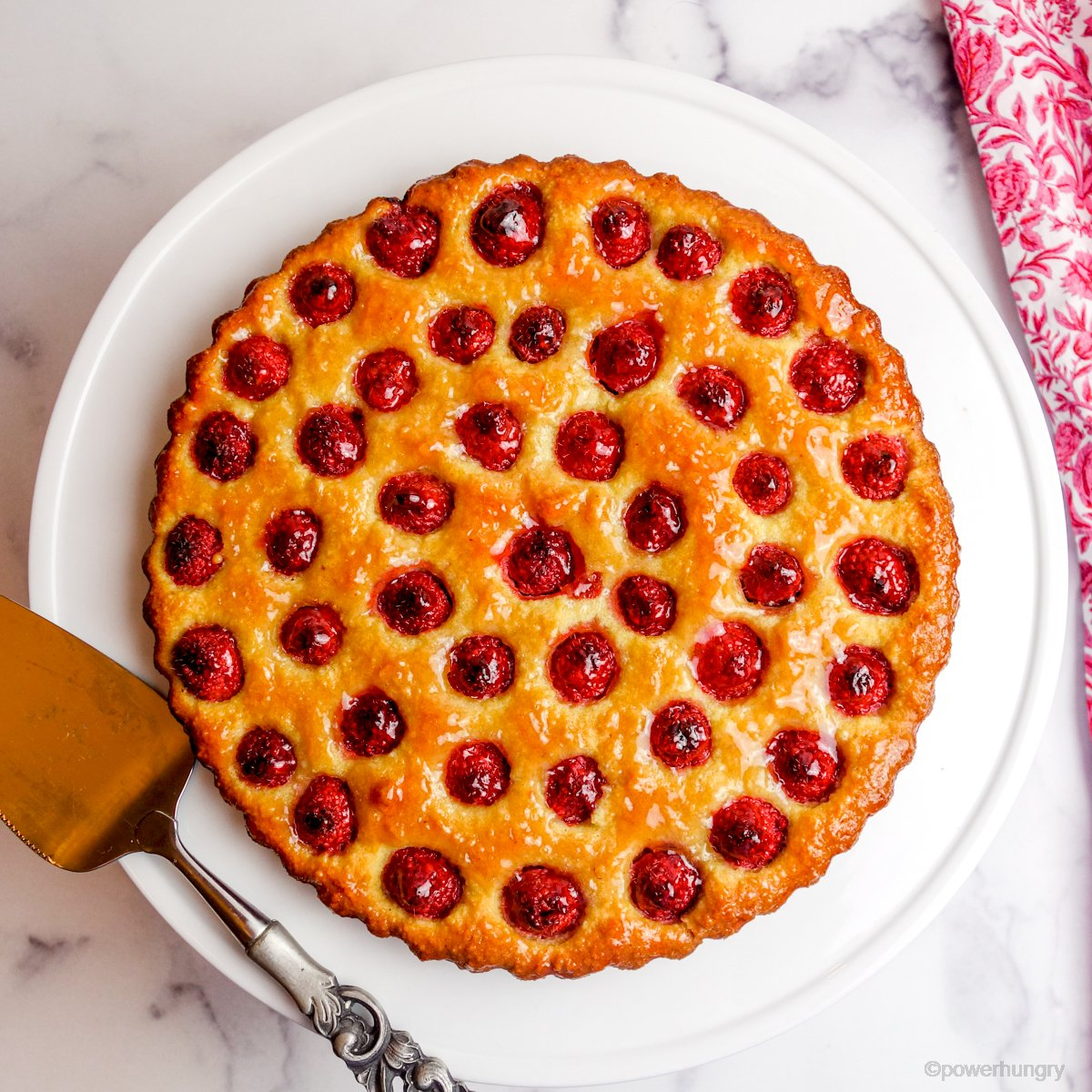 vegan no-crust raspberry almond tart on a white cake plate and a pink and white napkin alongside