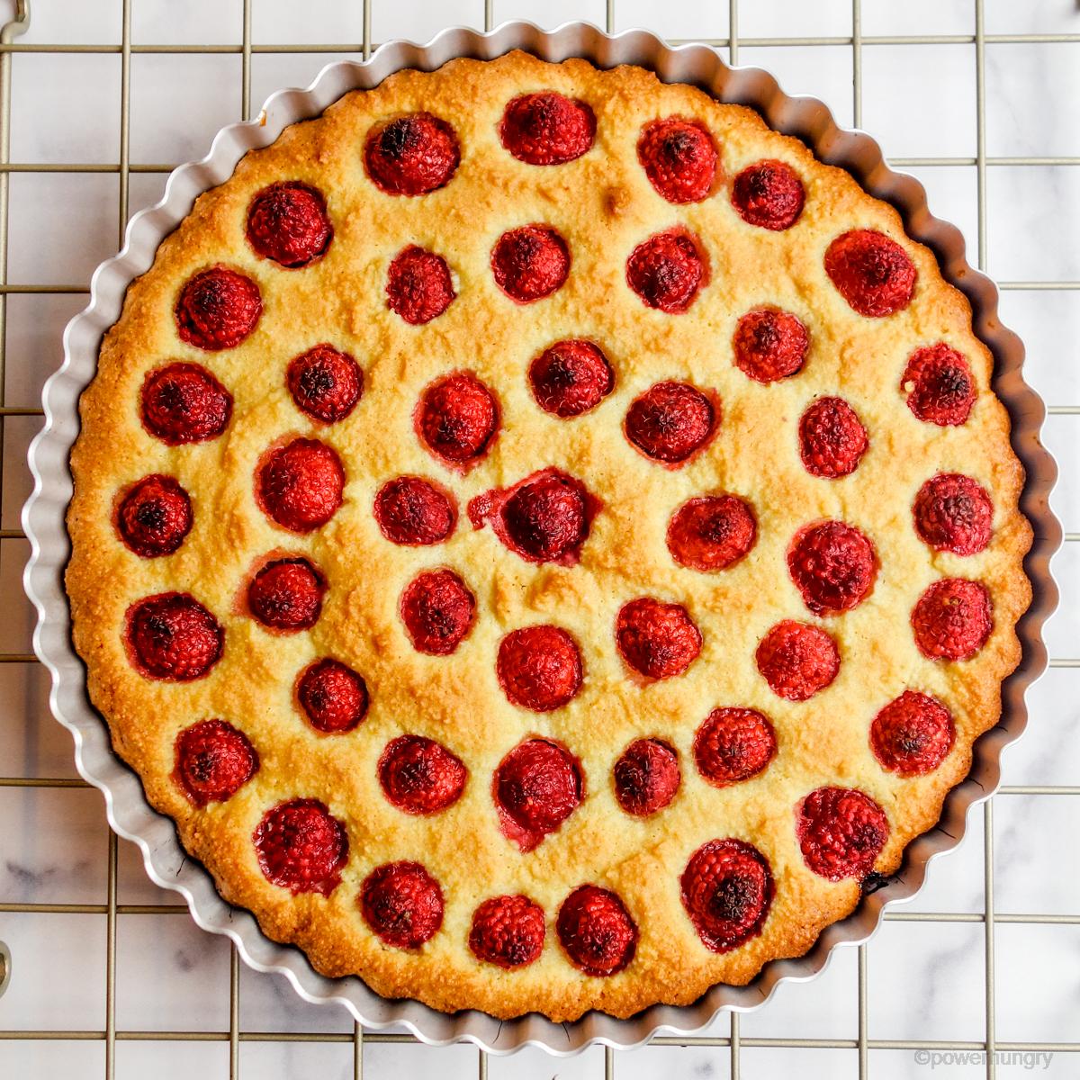 baked vegan raspberry tart cooling on a cooling rack