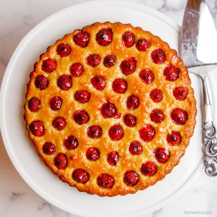 baked vegan no-crust raspberry almond tart on a white cake plate