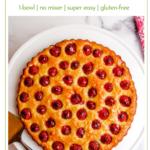 vegan raspberry almond tart on a white cake stand