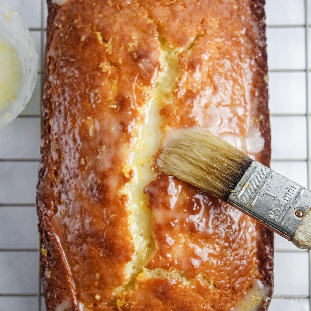 overhead shot of vegan lemon loaf geting a lemon glaze brushed on top