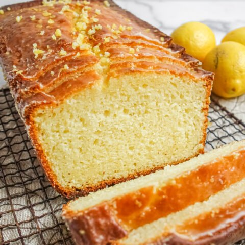 VEGAN GRAIN-FREE LEMON LOAF, partially sliced, on a wire cooling rack