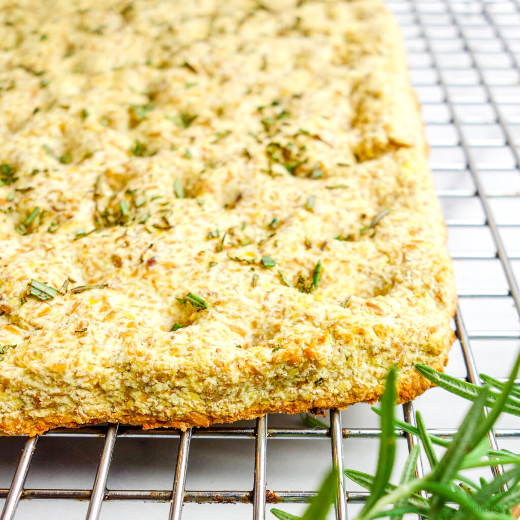 Close up of the corner edge of coconut flour focaccia on a silver cooling rack