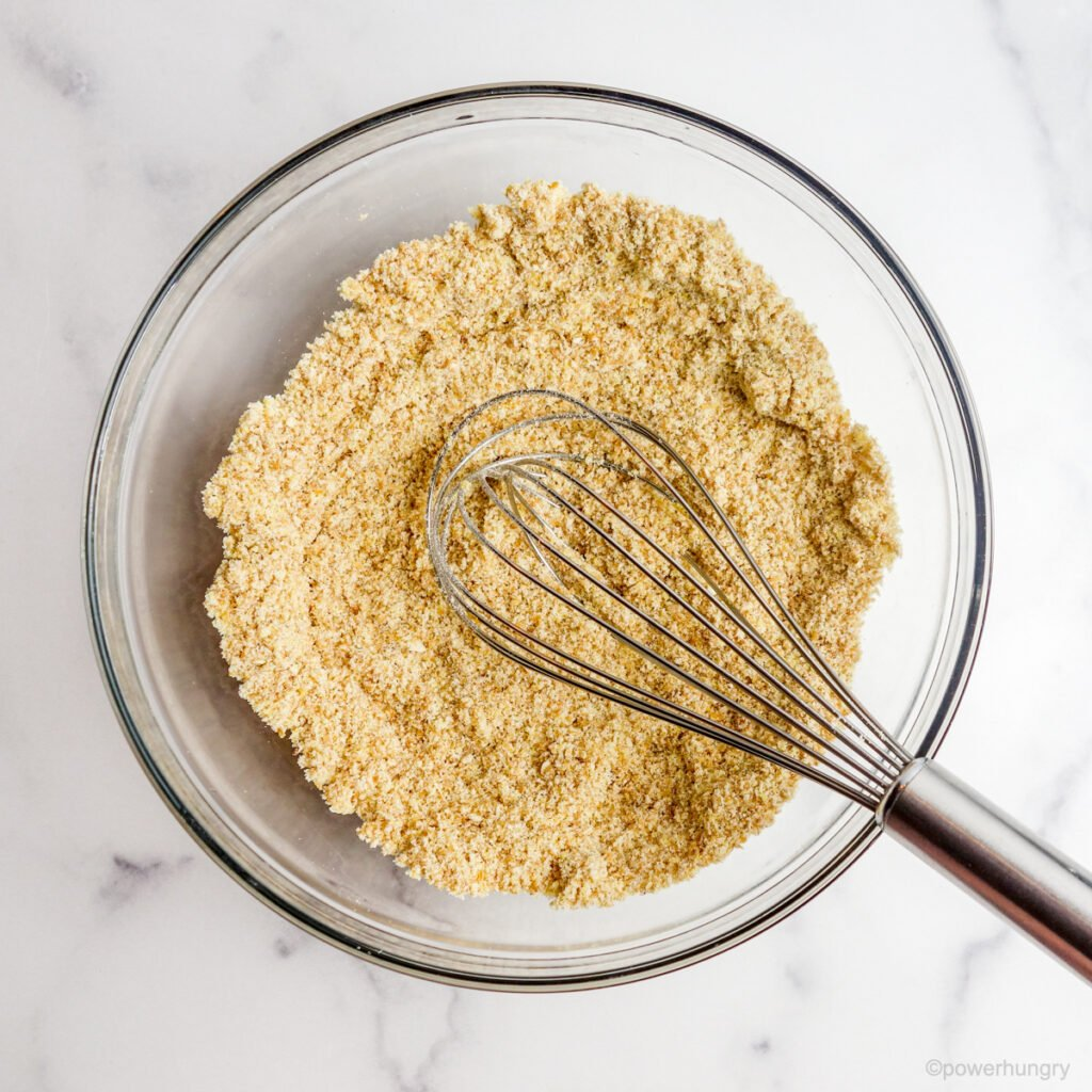 Overhead shot of glass bowl filled with ingredients for coconut flour flatbread